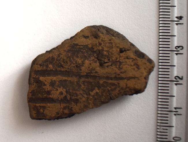 Археологія. Фрагмент стінки ліпної гончарної посудини, орнаментованої прокресленими горизонтальними смугами. Доба бронзи.